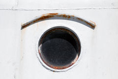 Old round porthole on white ship hull Royalty Free Stock Images
