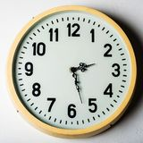 Old round station clock on the white wall.  Royalty Free Stock Images