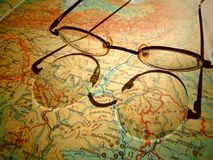 Old round vintage glasses laying on a map of Europe with hard shadow Stock Photography