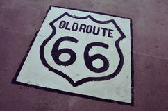 Old Route 66 sign on the asphalt. Stock Photo