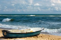 Old row boat on the sandy beach. Windy weather, waves in the sea. Old row boat on the sandy beach at sunny day. Windy weather, waves in the sea bay royalty free stock images