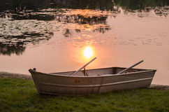 Old row boat. An old row boat sits on the shore at sunset Royalty Free Stock Photo