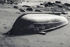 Old rowboat lays on sandy beach. Monochrome Stock Photos