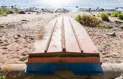 Old rowboat lays on a sandy coast Stock Photos