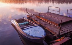 Old rowboat moored pier amazing sunset lake river Stock Photography