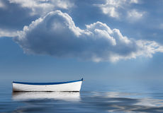 Old rowing boat marooned at sea. Concept image of loneliness, lacking direction, no leadership, rudderless, floating, listless or generally adrift without a goal Stock Photography