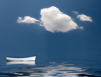 Old rowing boat marooned at sea. Concept image of loneliness, lacking direction, no leadership, rudderless, floating, listless or generally adrift without a goal Royalty Free Stock Image