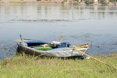 Old rowing boat moored on a river bank Royalty Free Stock Photo