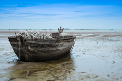 An old rowing boat in need of repair on the beach.  Stock Photo
