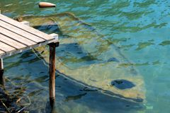 Old rowing boat under water at a wooden jetty Stock Photos