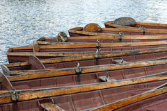 Old Rowing Boats. A line of old and worn, brown rowing boats. Fanned out on the river Royalty Free Stock Photo