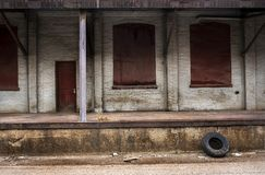 Old Rubber Car Tire Leaning Against Warehouse Loading Dock in City. Old Rubber Car Tire Leaning Against Closed Warehouse Loading Dock in City. Boarded up windows stock photo