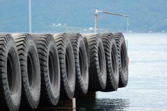 Old rubber tires as fenders on a pier.  stock photos