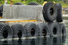 Old rubber tires as fenders on a stone pier.  royalty free stock photography