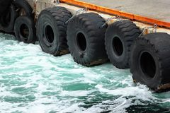 Old rubber tires as fenders on a stone pier.  stock images