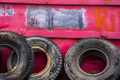 Old Rubber Truck Tires Leaning Against Pink Metal Trash Container in City. Old Rubber Truck Tires Leaning Against Pink Metal Junk Trash Container in City Factory royalty free stock photos