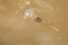 Old Rubbish Bulb in Dirty Yellow River Royalty Free Stock Photography