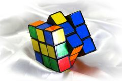 Old Rubik's cube on a white silk background. Stock Photo