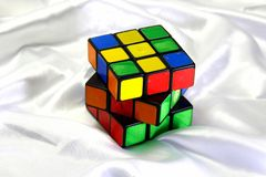 Old Rubik's cube on a white silk background. Stock Image