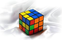 Old Rubik's cube on a white silk background. Royalty Free Stock Image