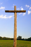 Old Rugged Cross and Horizon. An old, rugged wooden cross stands with the horizon behind against a deep blue sky with white clouds stock image