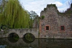 Old ruin with stone bridge on a small river. With weeping willow stock photo