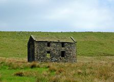An old abandoned stone farmhouse in green pasture on high pennine moorland with bright blue sky stock photos