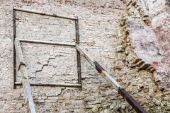 Old ruined aged brick wall. Weathered building facade supported by rusty iron construction.  royalty free stock photo