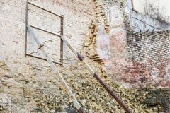 Old ruined aged brick wall. Weathered building facade supported by rusty iron construction.  stock image
