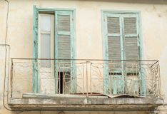 Old ruined balcony with blue wooden doors royalty free stock photo