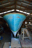 Old ruined boat awaiting restoration in a boat workshop. LEIGH, NZL - JAN 26 2016:Old ruined boat awaiting restoration in a boat workshop.New Zealand is known to Royalty Free Stock Photos