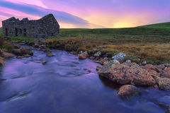 An old ruined bothy on a Scottish moor and a creek flows through Royalty Free Stock Photos