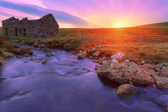 An old ruined bothy on a Scottish moor and a creek flows through Stock Photography