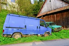 Old ruined cars. Ruined delivery van and car. Rusty van and car covered with moss. Stock Photos