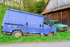 Old ruined cars. Ruined delivery van and car. Rusty van and car covered with moss. Stock Image