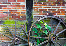 Old ruined cartwheels at wall of farm house Stock Photo