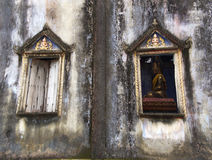 Old and ruined. Church with the Buddha statue is inside when looking through the windows Stock Images