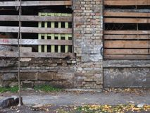Old ruined city fence, the columns of orange bricks and boards of boards. Stock Photos