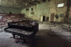 Old ruined grand piano in a concert hall in the city of Pripyat: collapsed rows of chairs, green walls, a broken wooden stage, a z. One of radioactive danger Royalty Free Stock Photos