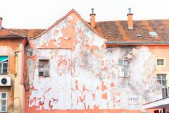 Ruined house facade. An old and ruined house facade with peeled off paint and destroyed outside walls royalty free stock photo