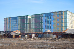 Old ruined industrial building on the background of the new built residential complex Stock Images