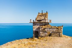Old ruined lighthouse on a cape. Lighthouse without windows and doors royalty free stock images