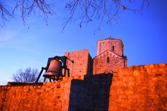 Old ruined monastery and bell. An old ruined monastery and an iron bell on the wall stock images
