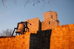 Old ruined monastery and bell. An old ruined monastery and an iron bell on the wall royalty free stock photography