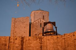 Old ruined monastery and bell. An old ruined monastery and an iron bell on the wall stock image