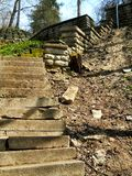 Old ruined stairway running down from the hill Stock Photo
