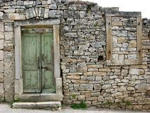 Old ruined stone made wall with green door and window frame in Zminj in Istria,Croatia Stock Photos