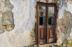 Old ruined wooden door in grungy facade of ruin house. Sunny day Stock Photos