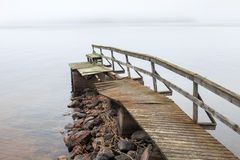 Old ruined wooden pier in foggy morning Stock Photos