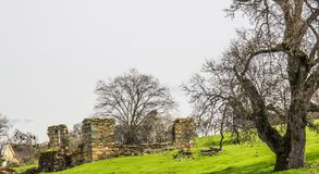 Old Ruins Of Stone House. On Side Of Grassy Hill Stock Photo